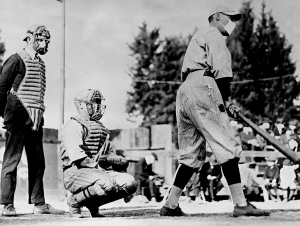 """John """"Beans"""" Reardon, left, wearing a flu mask underneath his umpire's mask, prepares to call a pitch in a California Winter League game on January 26, 1919, in Pasadena, California. During a global influenza pandemic, all players and fans were required by city ordinance to wear facial coverings at all times while outdoors. The catcher and batter's identities are unconfirmed, but the best available evidence suggests it might be Truck Hannah behind the plate and Rube Ellis at bat."""