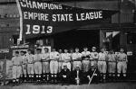 "Past and present members of the Thomasville Hornets pose with the team's Empire State League pennant before the start of the 1914 season. Standing, left to right: Mitchell Davenport, Klump, Harry Champlin, ""Red"" Murch, Mabry, Manager Martin Dudley, Hal Barnett, George Wilkes, Hall, Vincent Roth, ""Professor"" Day, Schultz, Ealen, Telken, Kane. Front row, left to right: E. R. Jerger, Club Secretary; R. G. Mays, club president (1914); J. B. Jemison, club president (1913)."