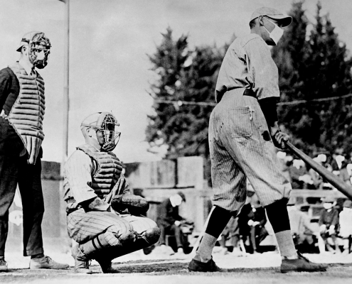 "John ""Beans"" Reardon, left, wearing a flu mask underneath his umpire's mask, prepares to call a pitch in a California Winter League game on January 26, 1919, in Pasadena, California. During a global influenza pandemic, all players and fans were required by city ordinance to wear facial coverings at all times while outdoors. The catcher and batter's identities are unconfirmed, but the best available evidence suggests it might be Truck Hannah behind the plate and Rube Ellis at bat."