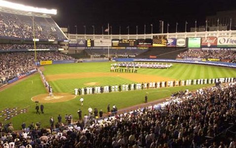 A large American flag is unfurled on the outfield by SUNY Maritime Academy cadets as the Yankees and Devil Rays are joined by members of the New York City Fire Department, EMS and Police Department during ceremonies honoring the victims of the World Trade Center terrorist attack. (COURTESY OF MLB.COM)