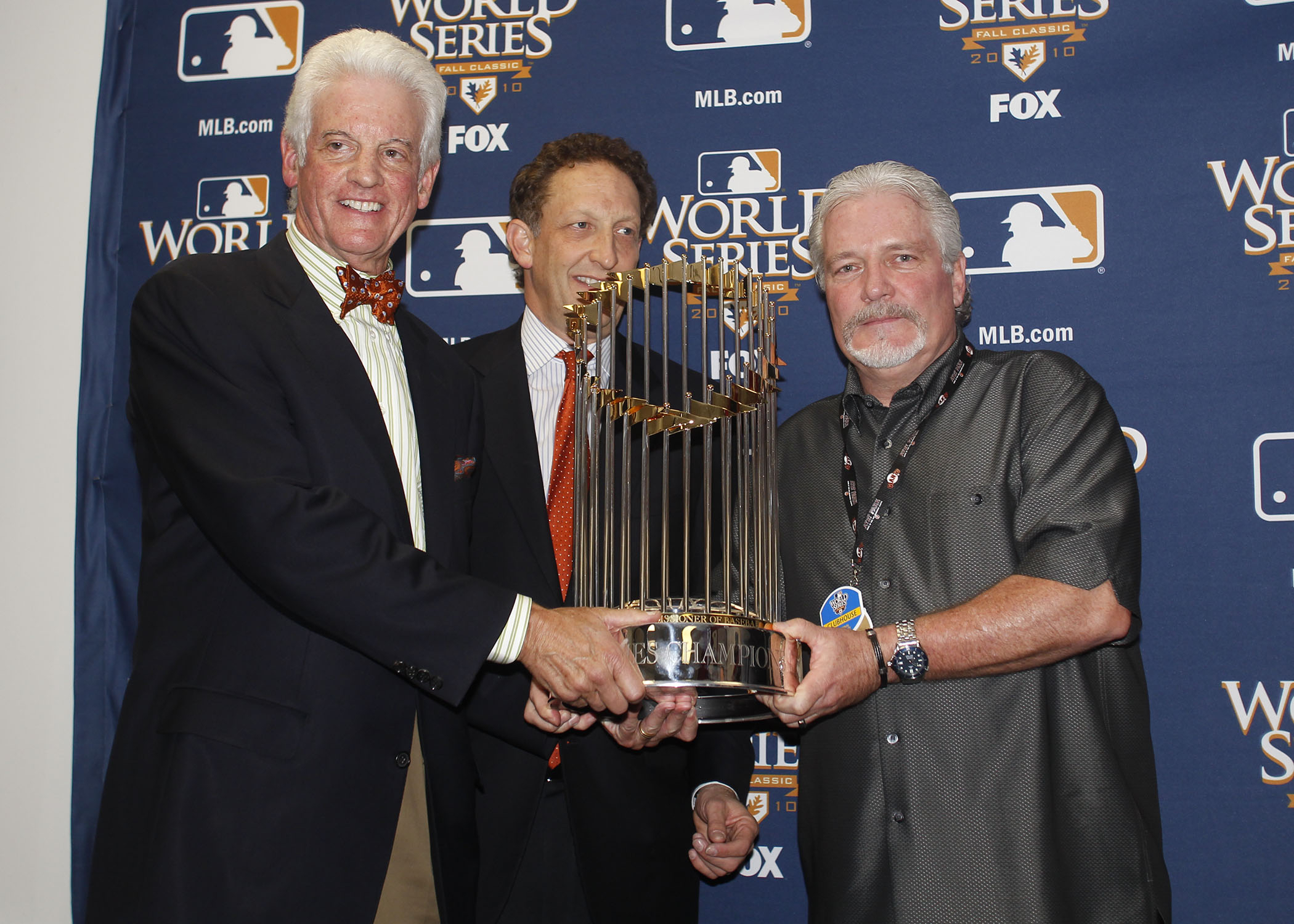 San Francisco Giants GM Brian Sabean, right, is presented with the 2010 World Series trophy by Giants owners Bill Neukom, left, and Larry Baer, center, on November 1, 2010. (SAN FRANCISCO GIANTS)