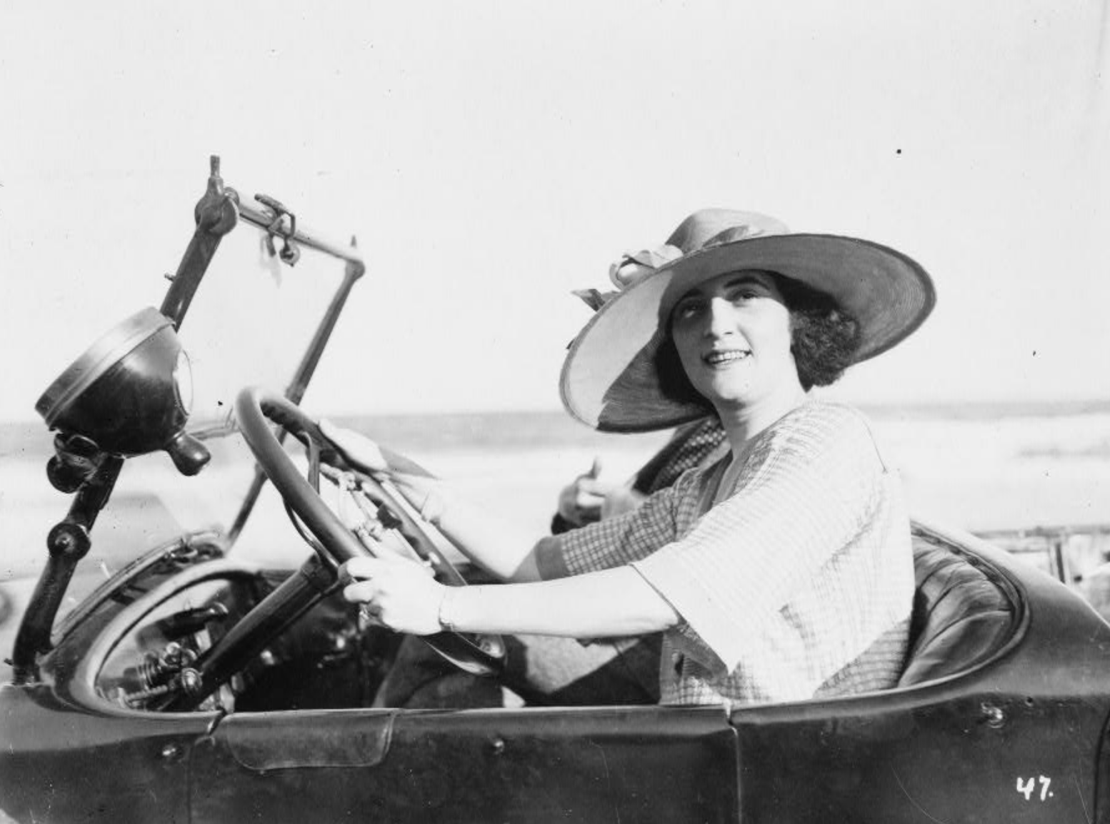 A woman sits behind the wheel of an automobile, circa 1921 (LIBRARY OF CONGRESS)