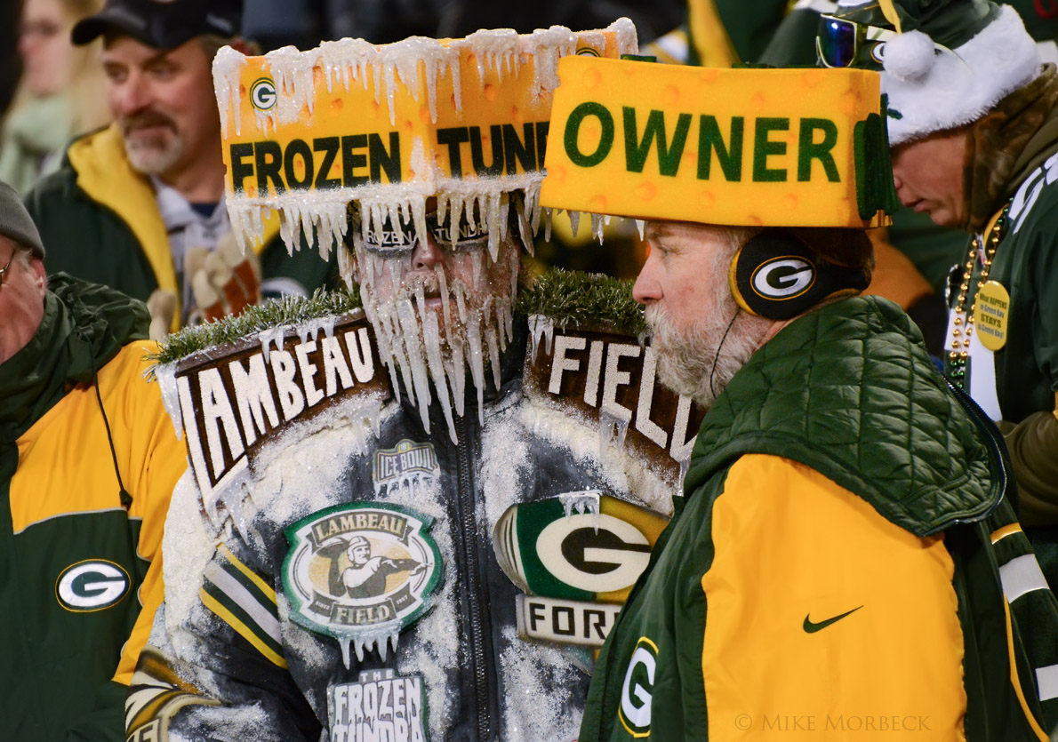 """Green Bay Packers fans, sporting cheese-wedge hats, one of which reads """"OWNER."""" (Photo by Mike Morbeck/Creative Commons)"""