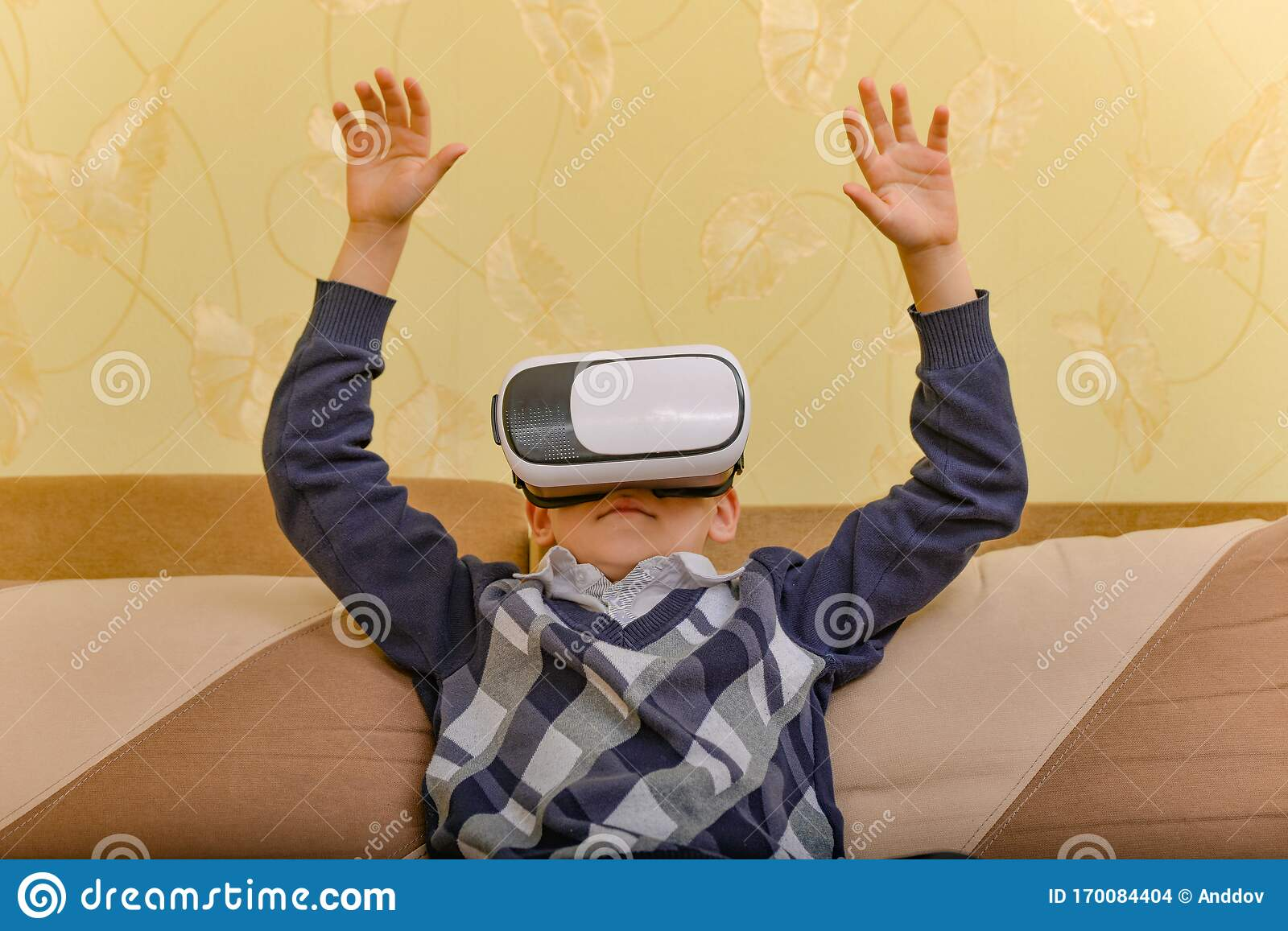"""A young boy does """"the Wave"""" as a digital spectator to a baseball game, from his own couch at home. (ANDRIY DOVZHYKOV / DREAMSTIME.COM)"""