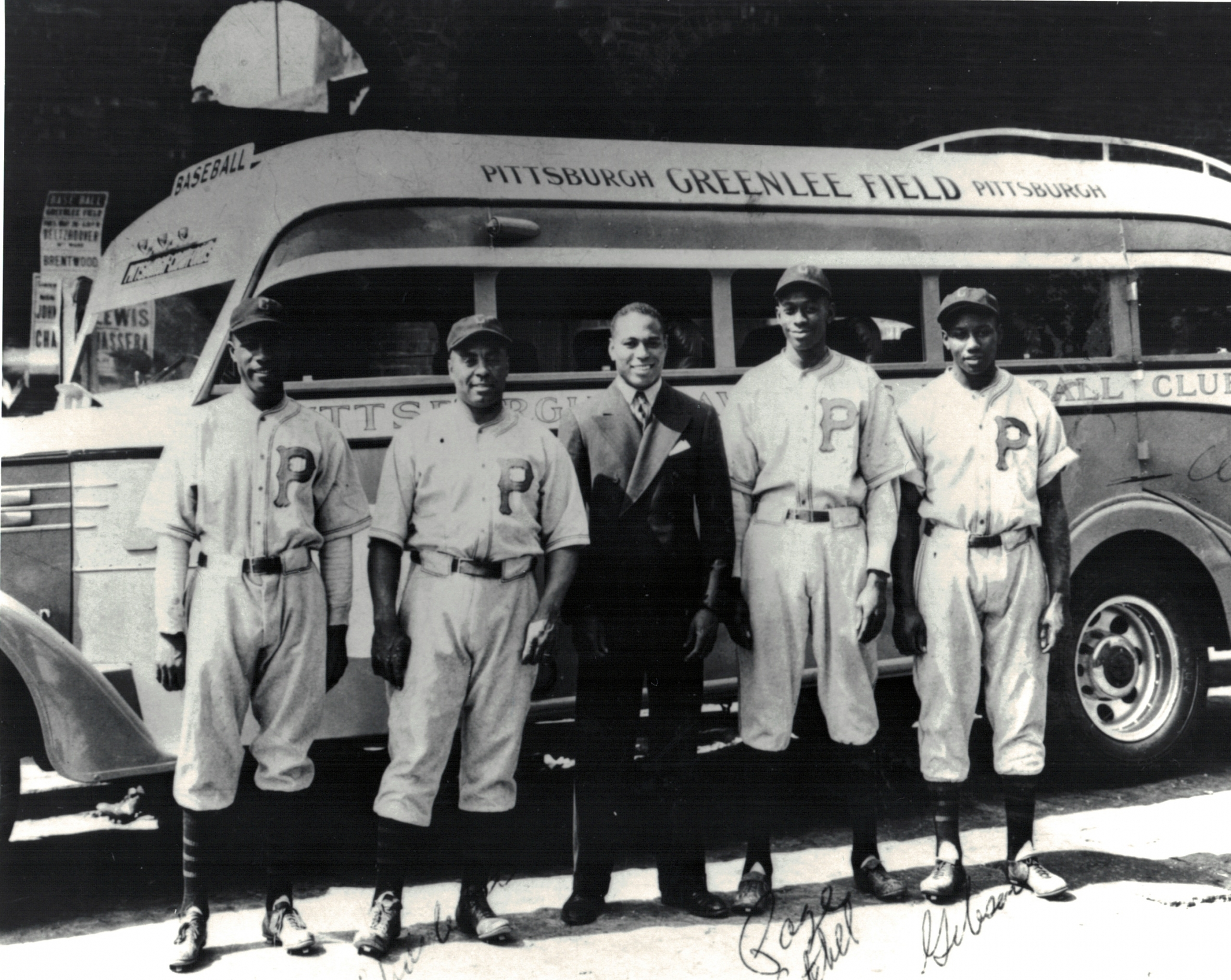 From left, Leroy Matlock, Oscar Charleston, boxer John Henry Lewis, Satchel Paige, and Josh Gibson pose in front of the team bus at Greenlee Field in Pittsburgh. (NOIRTECH RESEARCH, INC.)